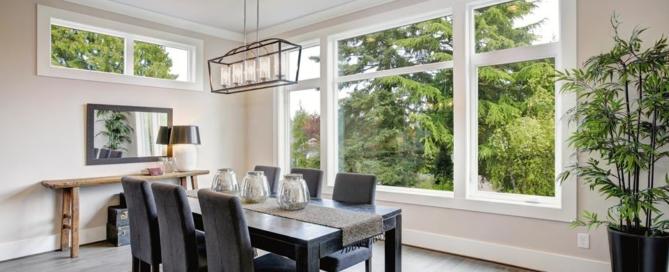 Projekt wnętrza – aranżacja jadalni z dużym stołem i oknami wychodzącymi na ogród z drzewami.